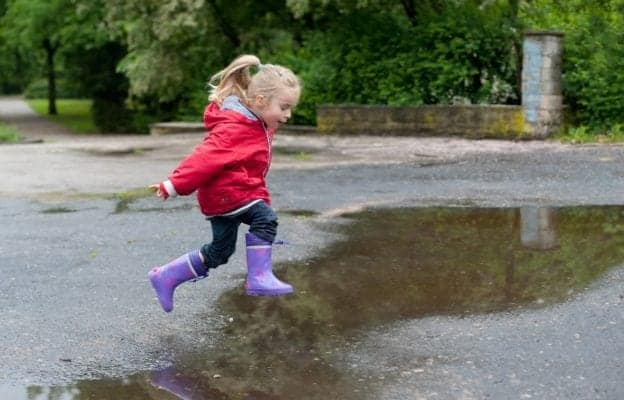 Kid jumping in a puddle in the rain