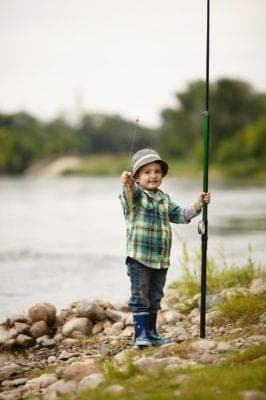 Little boy showing off the fish he caught