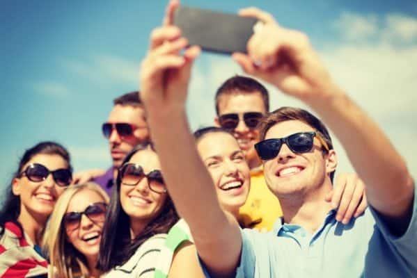 Group of smiling people taking a selfie