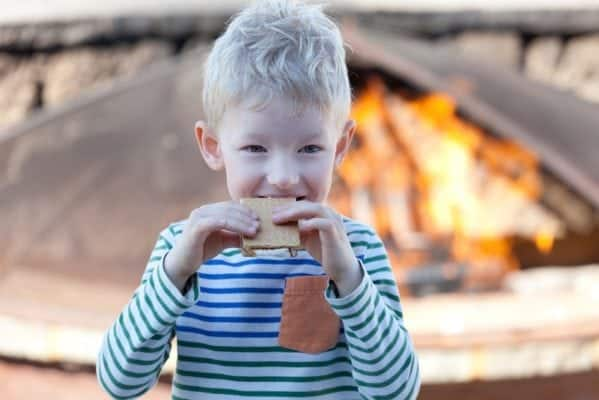 Little boy eating smores by the firepit