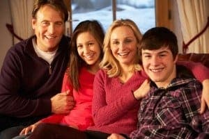 family posing on the sofa in front of a winter backdrop in a Pigeon Forge cabin with internet access