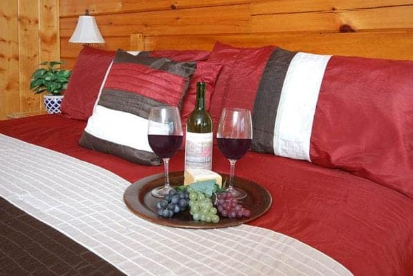 Wine and grapes on the bed of Eagles Perch, one of our Pigeon Forge mountain cabins.