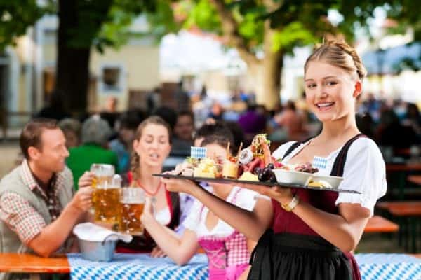 A waitress with a tray of food at an Oktoberfest celebration.