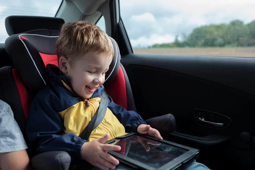 little boy playing in car with tablet