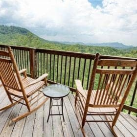 Chairs on the deck of a luxury Gatlinburg cabin with mountain views.
